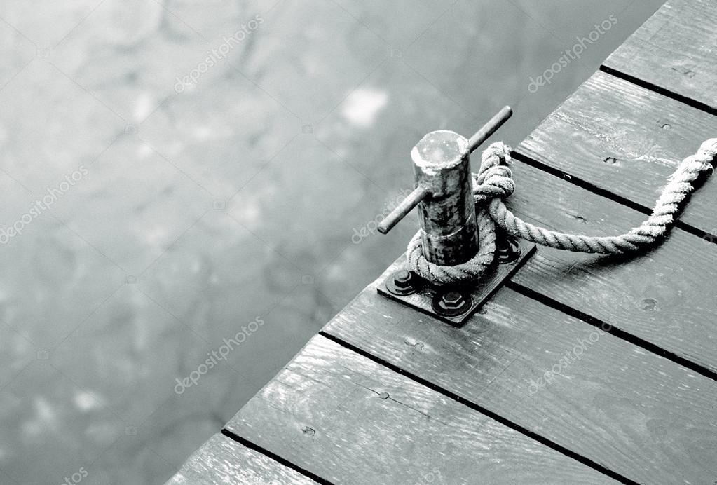 Taut ropes to a bollard on a pier