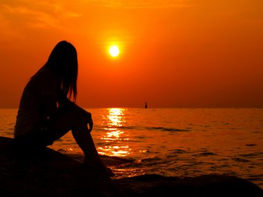 A woman alone watching the sunset