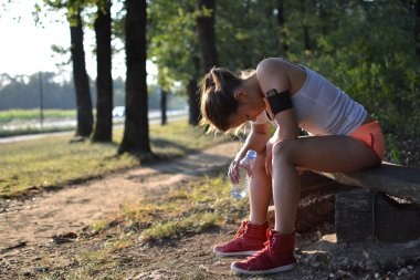 Young woman resting in the park after the workout