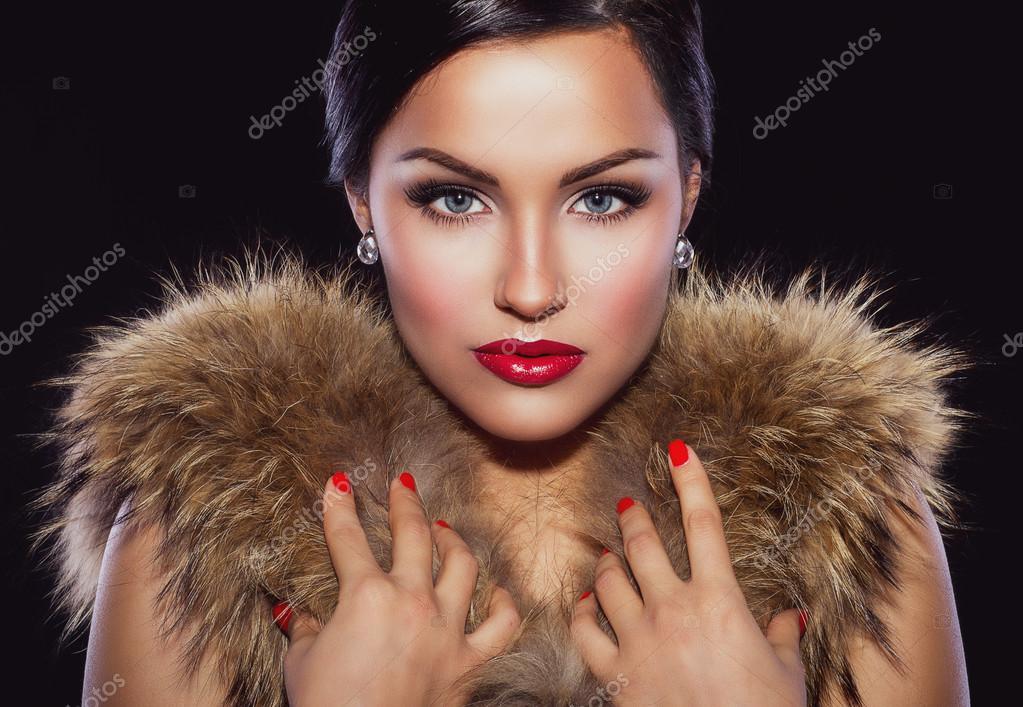 Beautiful brunette holding her hands on fur