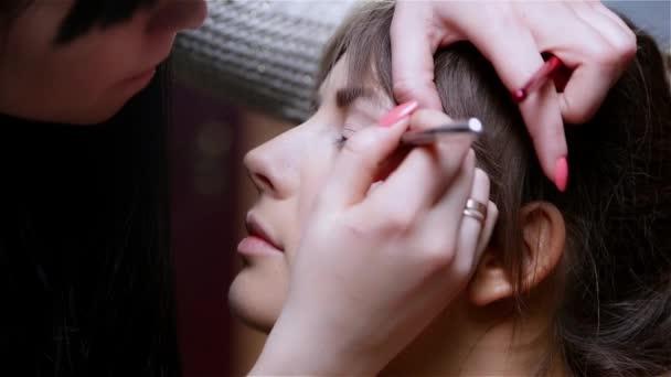 žena v salonu krásy, oční linky, make-up dělá