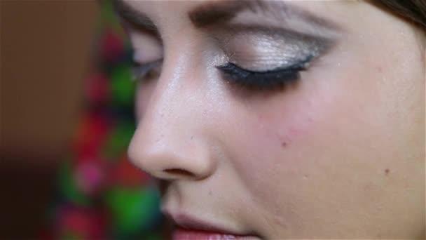 dívka ukazuje její malované oční make-up