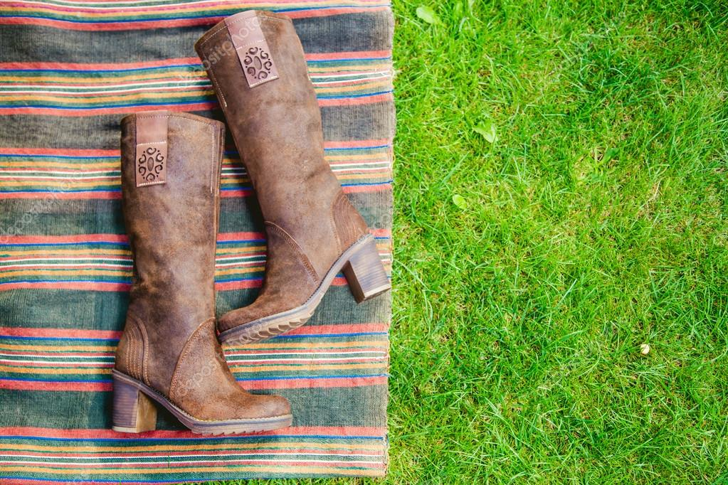 Suede boots women lie on the grass