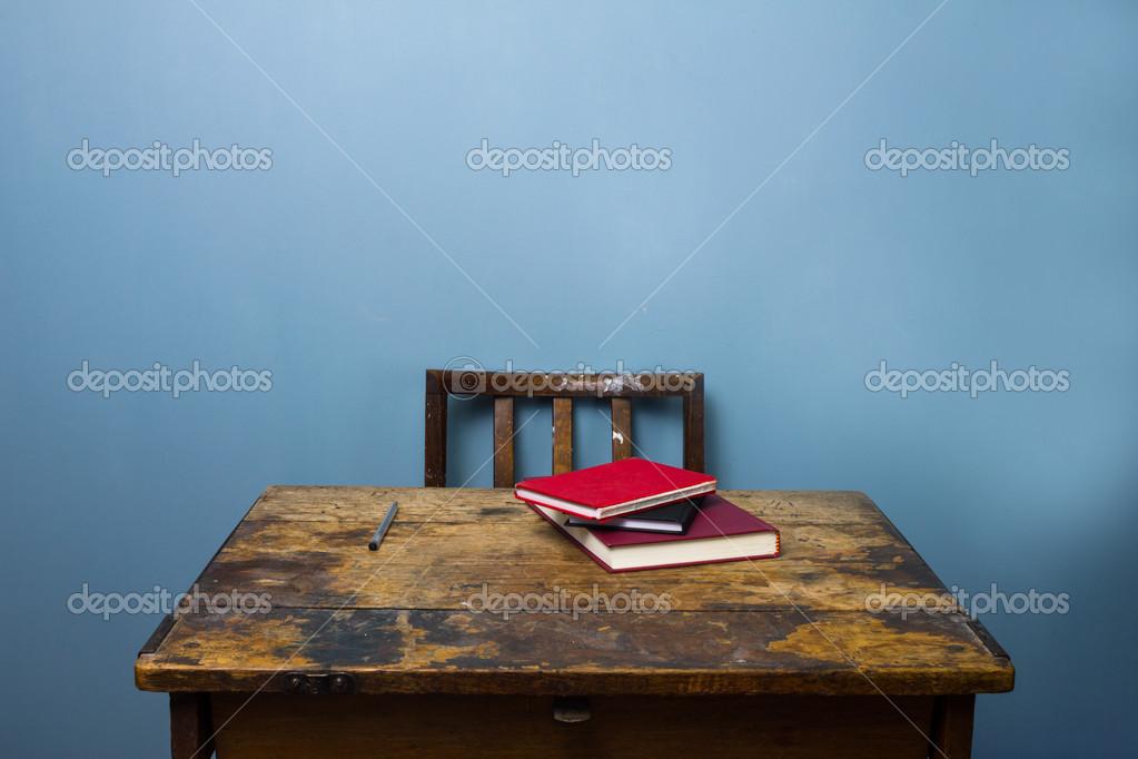 Vieux bureau en bois et chaise avec livres et un stylo