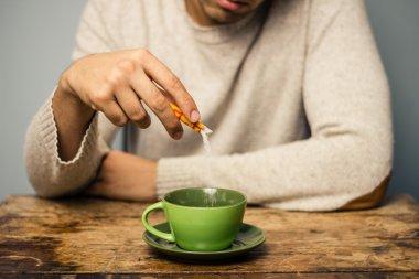 Man adding sugar to his coffee or tea