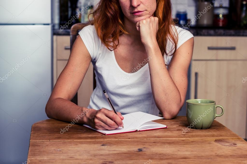 woman making a shopping list in her kitchen stock photo
