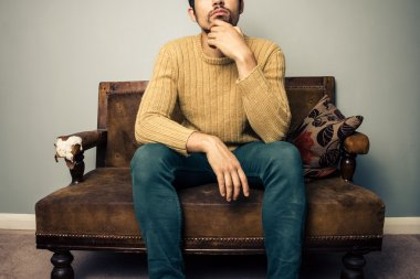 Young man on old sofa is thinking