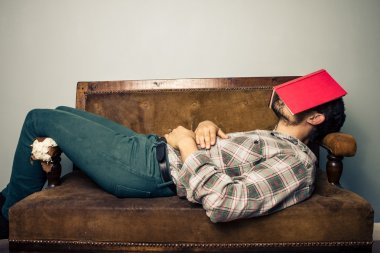 Man sleeping on old sofa with book covering his face