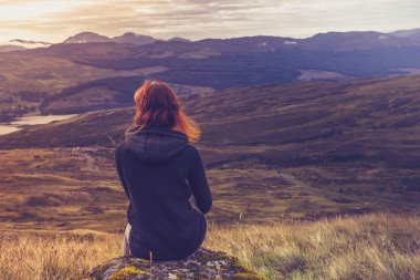 Woman sitting on mountain top and contemplating