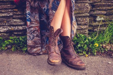 Woman's legs and hiking boots by stone wall