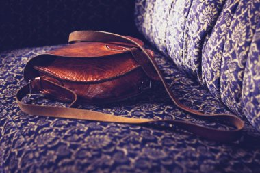 Leather handbag on vintage sofa