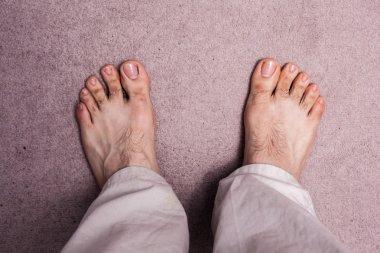 Man's bare feet on carpet