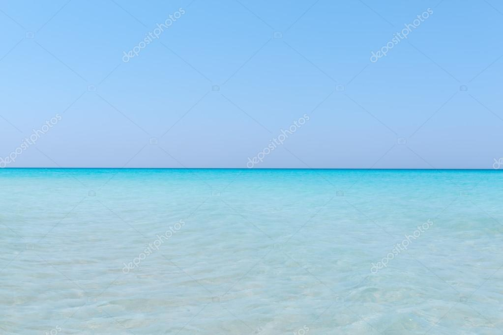 Turquoise tranquil ocean merging with clear beautiful sky at horizon line on sunny warm day
