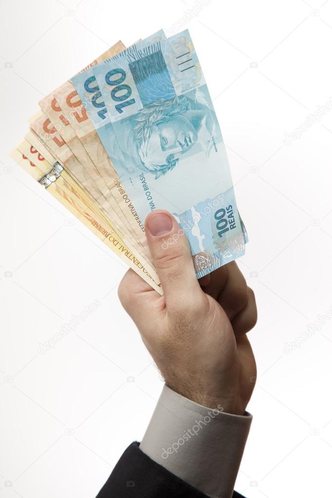 holding a Brazilian money.