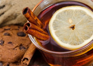 Close up of a glass mug of hot drink with a lemon and cinnamon stock vector