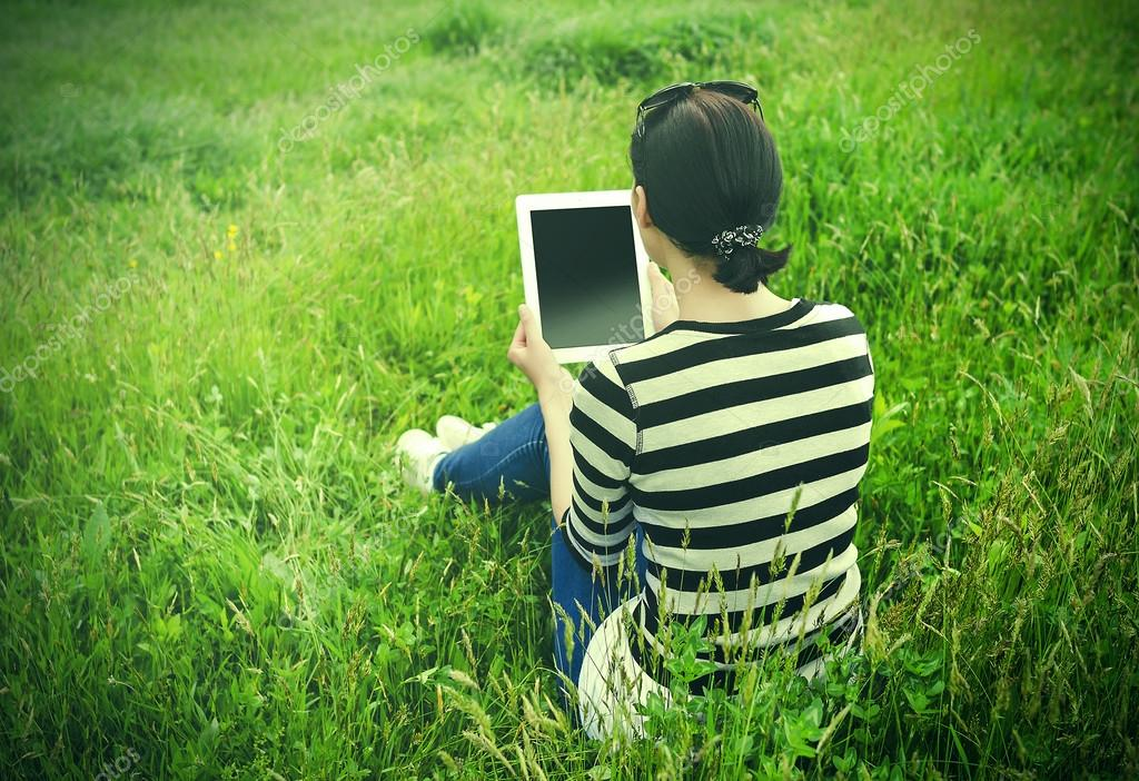 Girl with tablet in park on grass.