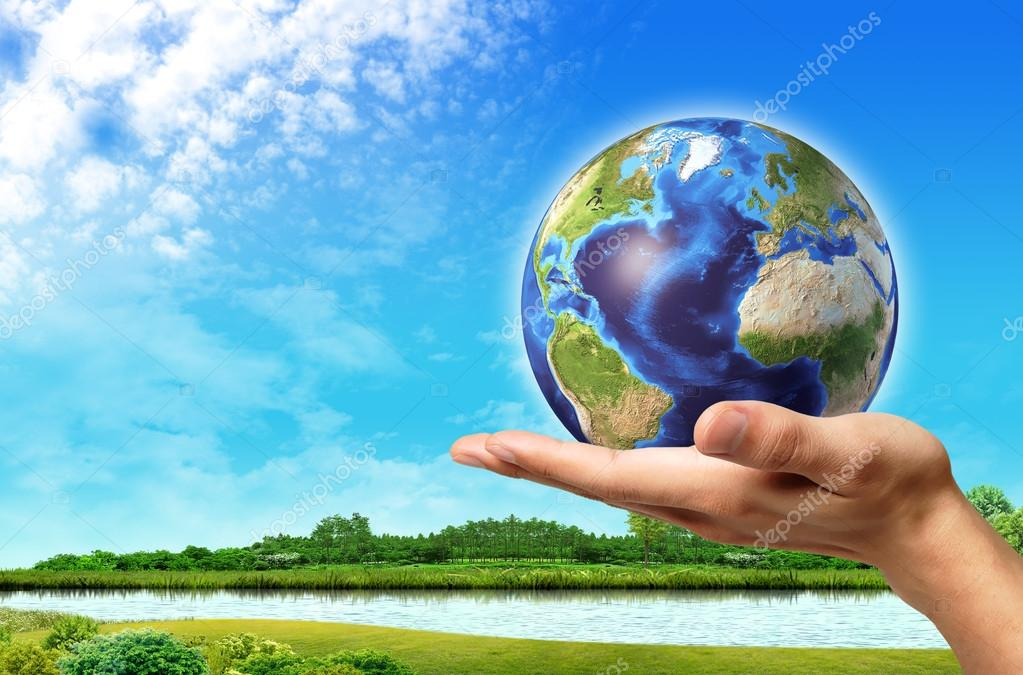 Man hand with earth globe on it and a beautiful green landscape