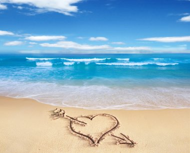 Heart with arrow, as love sign, drawn on the beach shore, with t