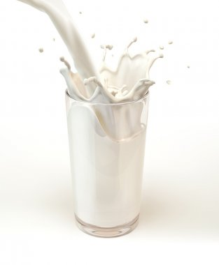 Fresh milk pouring into a glass with splash.