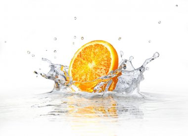 Orange slice falling and splashing into clear water.
