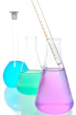 Volumetric laboratory glassware containing colored liquids