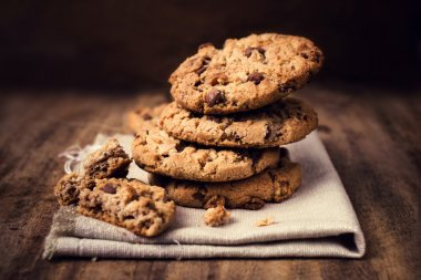 Chocolate cookies on white linen napkin on wooden table.