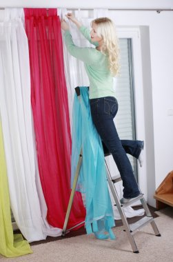 Woman on a ladder hangs up curtains