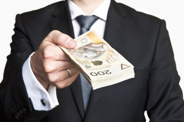 Businessman in suit and tie handing a lot of money