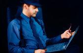 Muž s kloboukem a potrubí při pohledu na notebook
