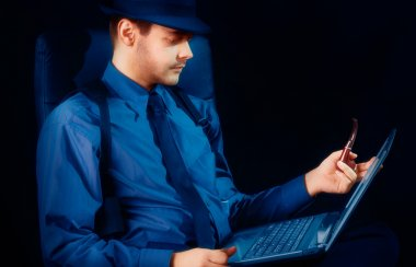 Man with Hat and Pipe Looking at Laptop