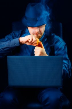 Man with Hat Lighting Pipe Looking at Laptop