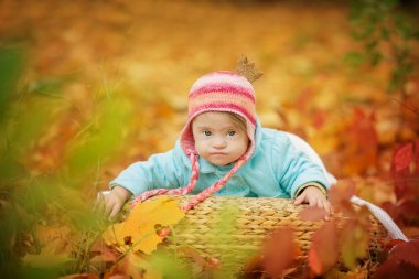 Baby with Down syndrome is resting in autumn forest
