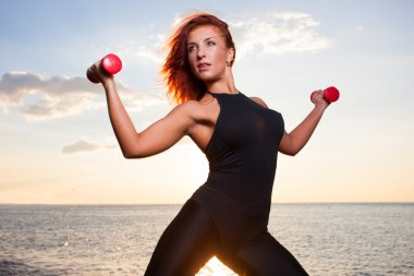 The girl does exercises with dumbbells