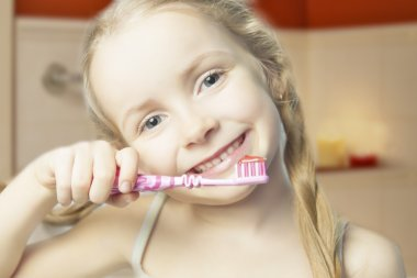 happy little girl holding toothbrush and smiling indoors