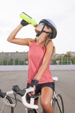 Cyclist woman takes a water break