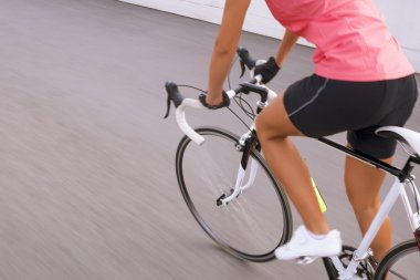 Female cyclist making excercise on race bike.