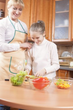 Young Caucasian Female Blond Teaching Her Daughter to Cook