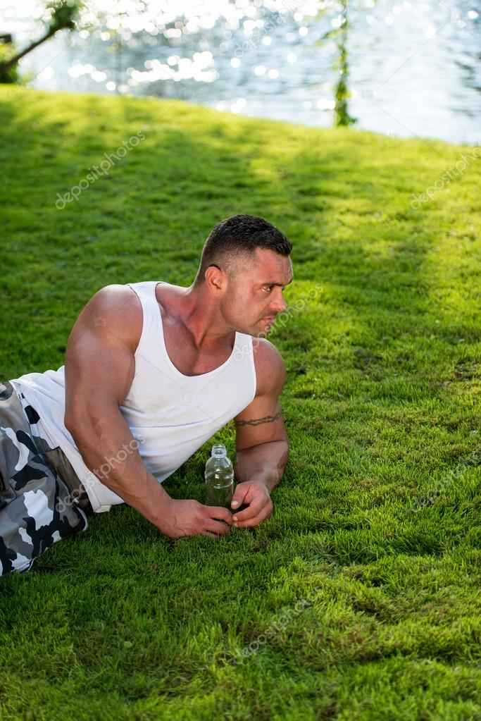 Bodybuilder Resting And Holding Water Bottle