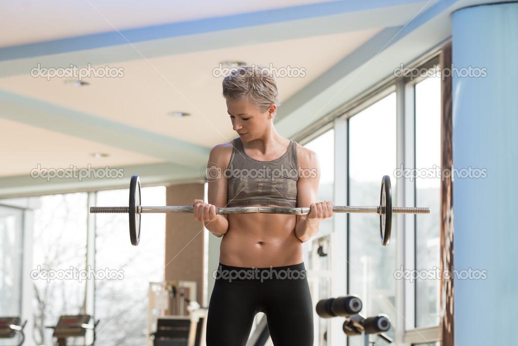 femme exercice biceps avec barre dans une salle de sport photographie ibrak 43338267. Black Bedroom Furniture Sets. Home Design Ideas