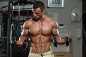 kulturista cvičení biceps s činkami