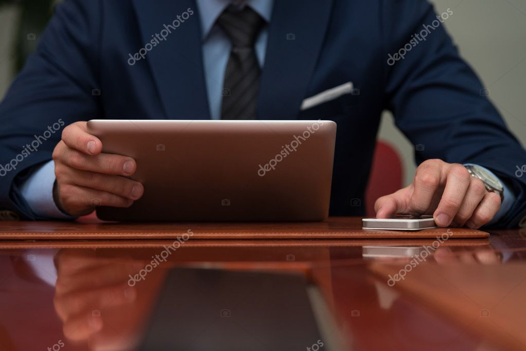 Close-Up Of Businessmen Using Touchpad