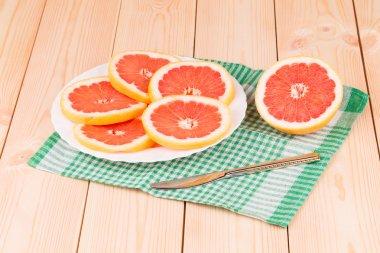 Portion of sliced grapefruit on plate.