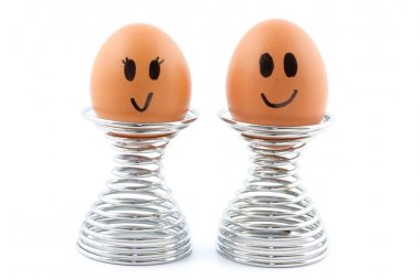 Two eggs in egg cups with happy faces stock vector