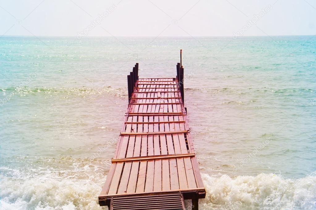 old wooden bridge in the sea in a retro style