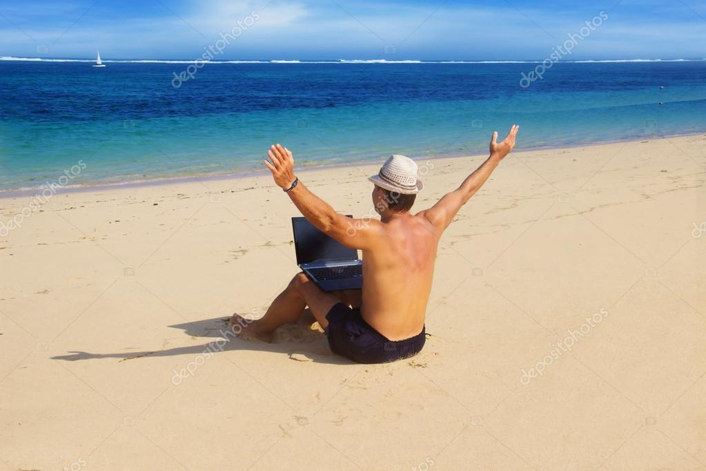 Man working with a laptop on the beach
