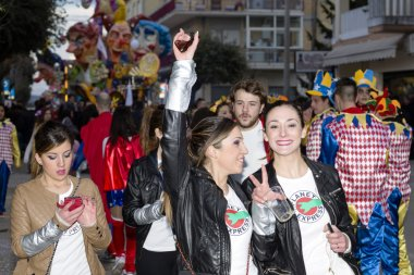 S.Egidio, Italy - March 2, 2014: Happy people having fun walking in the streets in the middle of masked people and carnival floats