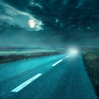 Driving on asphalt road at night towards the headlights