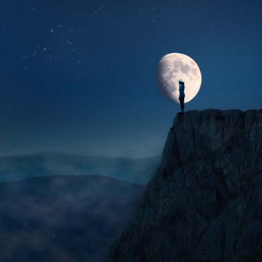 Lonely young woman on top of a cliff at night