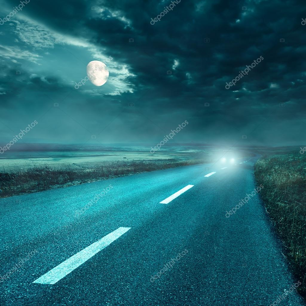 Driving on asphalt road at night towards the headlights