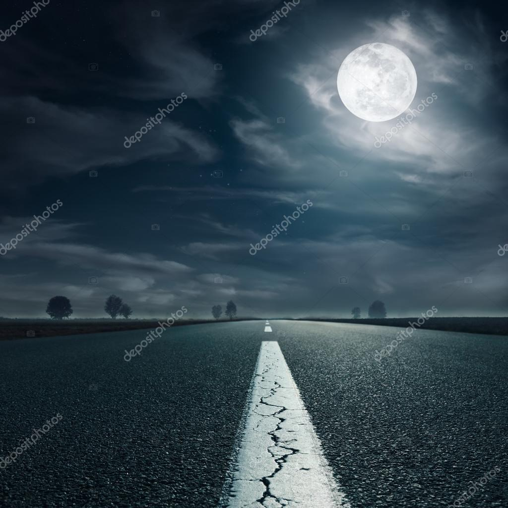 Driving on an empty highway towards the full moon